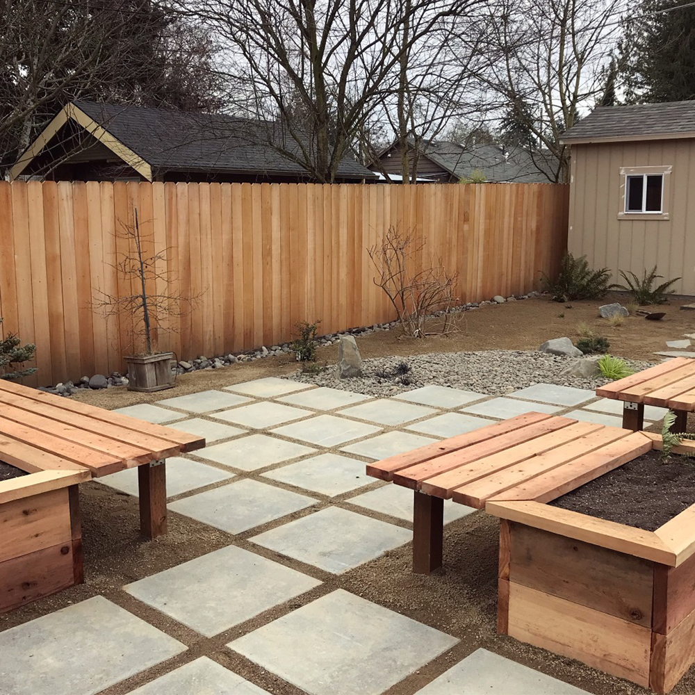 Low maintenance back yard design. Vancouver Bay paver patio with decomposed granite. Garden boxes with built in benches and minimalistic rock garden.